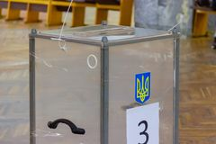 Взгляд голосований в урне для избирательных бюллетеней на станции голосования Избрание президента Украины Наблюдатели от различны стоковые изображения
