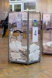 Взгляд голосований в урне для избирательных бюллетеней на станции голосования Избрание президента Украины Наблюдатели от различно стоковое фото