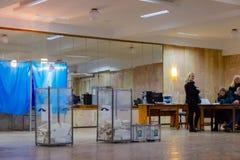 Взгляд голосований в урне для избирательных бюллетеней на станции голосования Избрание президента Украины Наблюдатели от различно стоковое изображение rf
