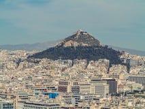 Взгляд города Афин с холмом Lycabettus на заднем плане взгляд города Афин с neighborhoo Plaka Стоковая Фотография