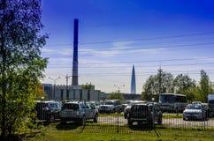 Взгляд города, больших труб и большого небоскреба на предпосылке парковки позади стоковые изображения rf