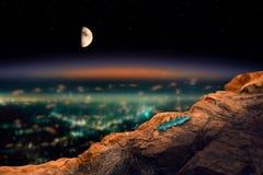 Взгляд города ночи от высокой скалы на которой лежит уединённый le стоковая фотография