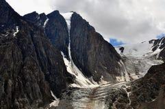 Взгляд горы Altai России - августа 2017 большой черных утесов и ледника малого Aktru в пасмурной погоде с малой частью сини Стоковые Изображения RF
