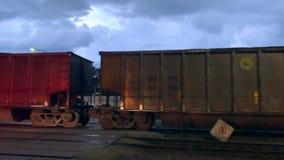 Взгляд груза нося товарного состава проходит скрещивание железнодорожной станции поезда прямого сообщения на Ardmore Ave в городс сток-видео