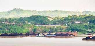 Взгляд движения буксиров вытягивая баржу угля на реке Mahakam, Samarinda, Индонезии стоковые изображения