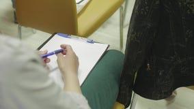 Взгляд девушек вручает держать пусковую площадку и ручку сочинительства на подолах видеоматериал