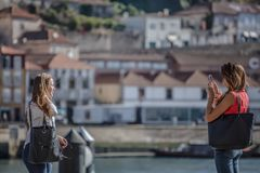 Взгляд 2 девушек принимая фото с мобильным телефоном, около реки с центром города на предпосылке стоковое фото rf