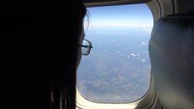 взгляд девушки детенышей 4K Азии красивый из окна самолета во время плоского полета видеоматериал