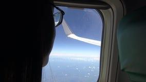 взгляд девушки детенышей 4K Азии красивый из окна самолета во время плоского полета акции видеоматериалы