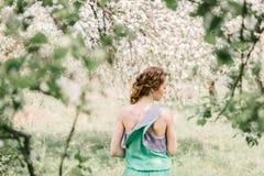 Взгляд девушки от задней части, весной в цветя orch яблока Стоковые Изображения