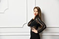 Взгляд девушки стильных и позитивности нося в черной сюите стоковое фото
