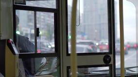 Взгляд для того чтобы повезти кабину на автобусе с женскими водителем и дорожным движением сток-видео