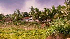 Взгляд дома за много деревьев - голубого неба при облака проходя, индийского дома в деревне сток-видео