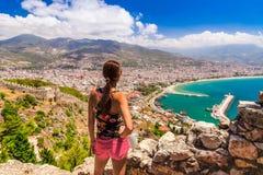 Взгляд женщины на ландшафте Alanya с Мариной и башней Kizil Kule красной в районе Антальи, Турции, Азии Известный турист стоковые изображения rf