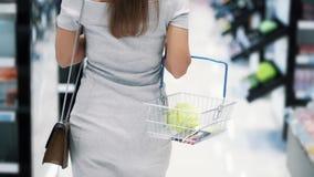 Взгляд задней стороны батокс женщины идет на косметический магазин, конец вверх, замедленное движение сток-видео
