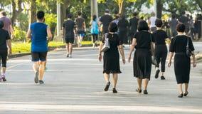 Взгляд задней части людей бежит и идет на пешеходный парк сада Стоковая Фотография