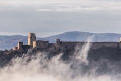 Взгляд замка Rocca Maggiore в Assisi Умбрии, Италии в середине тумана стоковое изображение rf