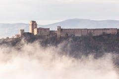 Взгляд замка Rocca Maggiore в Assisi Умбрии, Италии в середине тумана стоковые фотографии rf