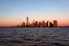 Взгляд захода солнца горизонта Нью-Йорка от шлюпки к острову Ellis стоковое изображение