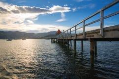 Взгляд захода солнца деревянной пристани в заливе Akaroa, около Крайстчёрча, Новая Зеландия стоковое изображение rf
