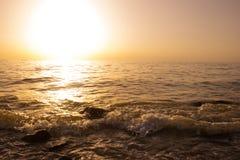 Взгляд захода солнца на стороне моря с ясным небом волны прибоя и большие камни валуна Оранжевая предпосылка с космосом экземпляр Стоковое Фото