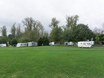 Взгляд зеленой лужайки с белыми фургонами рядом с путем стоковое фото rf