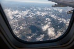 Взгляд земли через окно самолета Стоковые Изображения