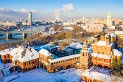 Взгляд зимы реки Moskva, моста Novospasskiy, и небоскребов на солнечном утре Krutitsy Metochion Лед, снег на крышах стоковая фотография