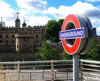 Взгляд знака станции метро и башни Лондона, Англии стоковая фотография
