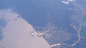 Взгляд из окна пассажирского самолета вниз к облакам и земле от высоты сток-видео