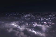 Взгляд из окна самолета к облакам вечером и вспышкам молнии стоковые изображения