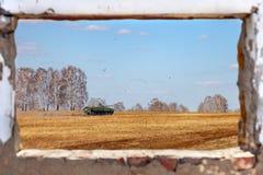 Взгляд из старого загубленного окна здания на зеленом танке на гусеницах едет в поле желтой травы во время Второй Мировой Войны стоковое изображение