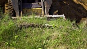 Взгляд канавы ведра бульдозера выкапывая в травянистой почве во время работ земли акции видеоматериалы