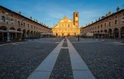 Взгляд квадрата Дукале с церковью Ambrogio в Vigevano на заходе солнца, провинции Павии, Италии стоковые фотографии rf