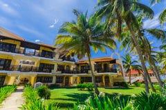 взгляд колониальных земель гостиницы, красивых приглашая ретро стильных зданий в тропическом саде на предпосылке голубого неба Стоковое Фото