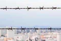 Взгляд колючей проволоки и города Стоковая Фотография