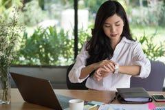 Взгляд коммерсантки на ее вахте на рабочем месте startup chec женщины Стоковое Изображение RF