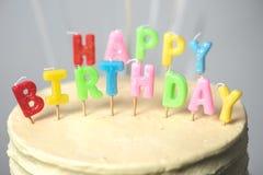 взгляд конца-вверх вкусного именниного пирога с свечами на праздничной таблице Стоковые Изображения