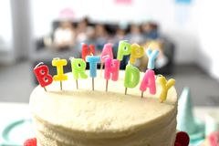 взгляд конца-вверх вкусного именниного пирога с свечами на праздничной таблице Стоковая Фотография