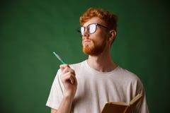 Взгляд конца-вверх думать бородатый молодой человек в белом владении футболки Стоковые Изображения