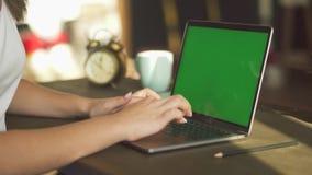 Взгляд конца-вверх женских рук печатая на ноутбуке с зеленым экраном дальше Женщина используя тетрадь с зеленым дисплеем на сток-видео