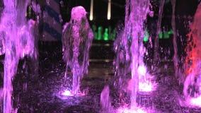 Взгляд конца-вверх красивого красочного фонтана на улице города вечером акции видеоматериалы