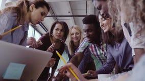 Взгляд конца-вверх молодой команды дела при женский руководитель группы работая совместно около таблицы, активно коллективно обсу акции видеоматериалы