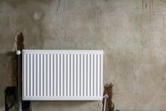 Взгляд конца-вверх нового изолированного установленного нагревая радиатора на стене кирпича грубой заштукатуренной в пустой комна Стоковое Фото