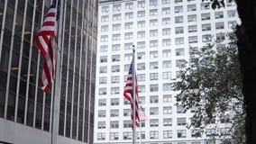 Взгляд конца-вверх офисов в небоскребах строя от стекла Американские национальные флаги развевая на ветре в Нью-Йорке видеоматериал