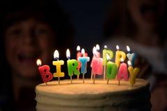 взгляд конца-вверх очень вкусного именниного пирога с горящими свечами Стоковые Изображения RF