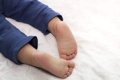 Взгляд конца-вверх пяток очень связал спать мальчика лежа на кровати стоковые изображения rf