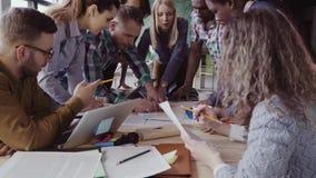 Взгляд конца-вверх смешанной группы лицо одной расы людей стоя около таблицы Молодая команда дела работая на проекте совместно сток-видео