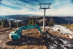 взгляд красивого ландшафта будучи построенным лыжного района, строительная площадка с экскаватором и машинное оборудование на нак Стоковые Фото