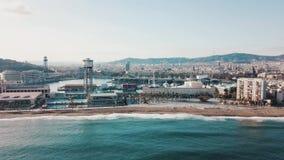 Взгляд красивого прибрежного города, современных зданий, волн моря бирюзы и людей идя на пляж против голубого неба акции видеоматериалы